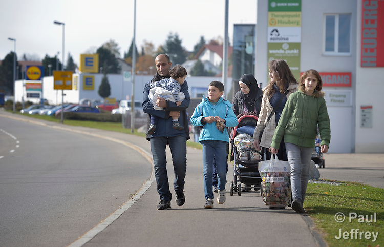 Syrian refugees walk on a street in Messstetten, Germany. They have applied for asylum in Germany and are awaiting word on the government's decision. Meanwhile, they live in a room in a former army barracks in Messstetten.