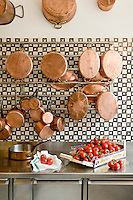 The kitchen display of copper pans and black and white tiles is in contrast with the black and white tiled wall and stainless steel worktop