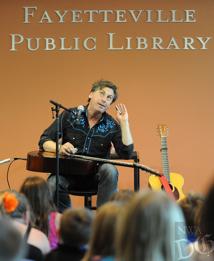 STAFF PHOTO ANDY SHUPE - Singer-songwriter Joe Crookston of Ithaca, Ny., performs Wednesday, July 9, 2014, during a concert for kids at the Fayetteville Public Library. Crookston will perform at 10:30 a.m. today at a family concert and conduct songwriting workshops during the day before hosting a culminating concert at 6:30 p.m. A concert is also planned for 7 p.m. Friday.