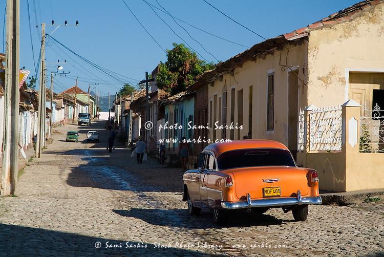 Classic American car driving in the cobblestone streets of Trinidad, Sancti Spiritus, Cuba.