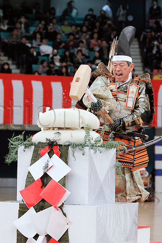 10.01.2011 Tokyo, Japan - Dressed in an ancient samurai warriors armor, former Japanese Foreign Minister Masahiko Komura swings a wooden mallet to crack layers of Kagami-mochi or glutinous rice cakes in a traditional Kagami-biraki ceremony to kick off new years first martial arts training at Tokyos Budokan Martial Arts Hall. The tradition of Kagami-biraki was originated in 15th century among samurais to officially start the first workout of the new year.