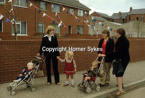 Protestant family women chatting in street Belfast  The Troubles Northern Ireland  Red white and blue bunting from house indicating that these women are in a protestant housing area. Orange Day Parade time. 1980s