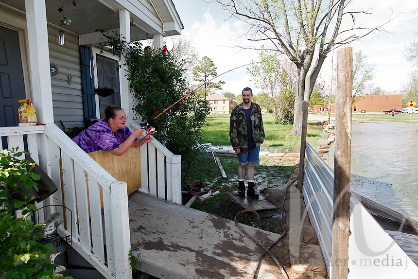 Laura Sandquist casts her fishing line into the Mississippi River floodwater from her home as family friend Ryan Hallam takes a break from sandbagging in the Red Star District of Cape Girardeau, MO, on Thursday, April 28, 2011.