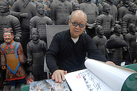 Yang Quanyi, 79, who was one of the original farmers who unerthed the Terracotta Army, signs books for a 1,000 rmb each month.  The 7,000 strong army of Terracota Warriors was unearthed in 1974.<br /> <br /> PHOTO BY RICHARD JONES/SINOPIX