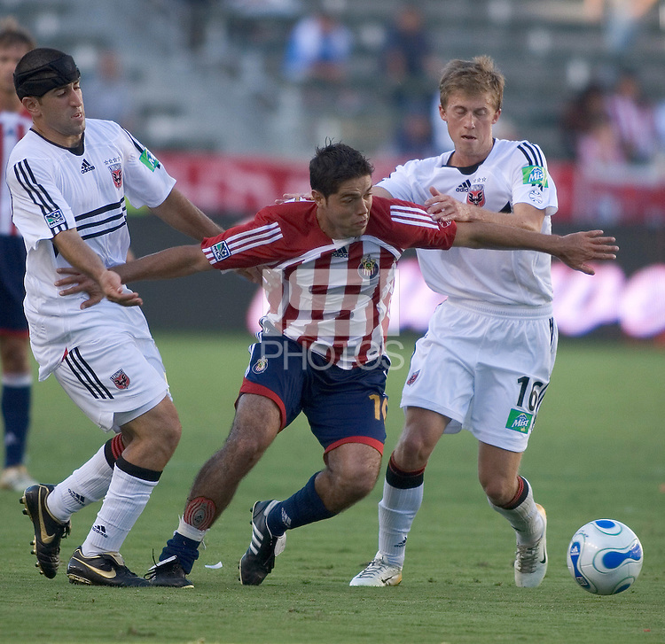 Chivas USA forward Juan Pablo Garcia  dribbles past D.C. United forward Alecko Eskandarian and midfielder Brian Carroll.  D.C. United defeated Chivas USA, 2-1, at the Home Depot Center in Carson, Calif. on September 3, 2006.