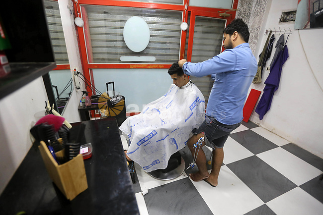 A Palestinian barber, Mahmoud Abu Shaweesh, 28, who was wounded in the leg during clashes with Israeli security forces at the Gaza-Israeli border, shave the head at his salon, in al-Nusairat refugee camp in the central Gaza Strip on May 24, 2018. Photo by Atia Darwish