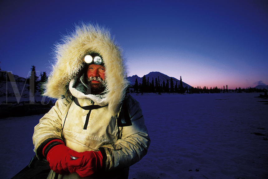 Portrait of an Iditarod musher in a fur-lined heavy coat, backlit by early morning light. Alaska.