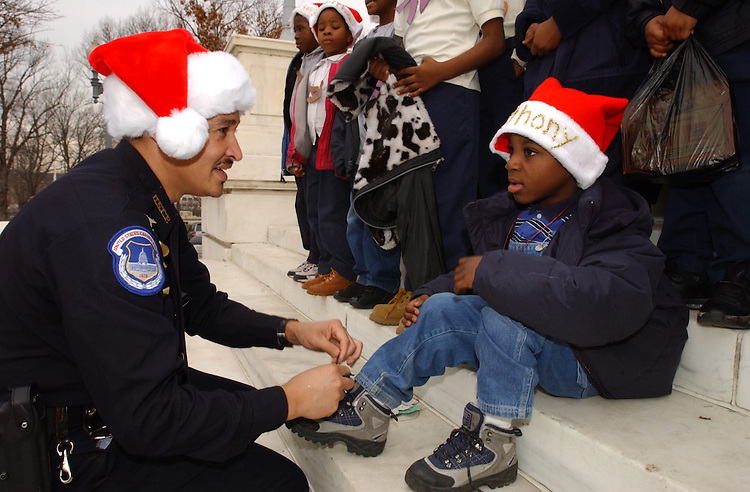 Chrismas2/120701 -- Capitol Police Office, G.S. Jackson ties Anthony Mease's shoe lace during the Second Annual Birney Elementary Chrismas Party sponsored by the United States Capitol Police.