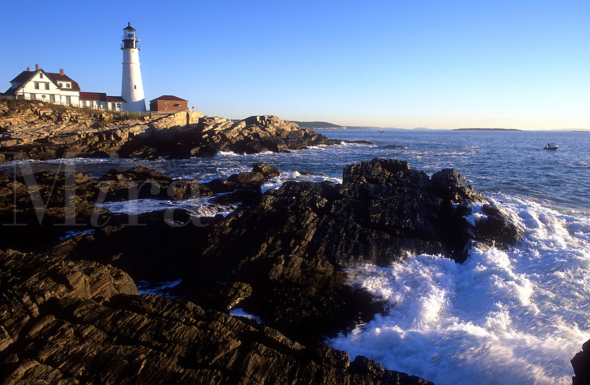 USA, Maine, Cape Elizabeth, Portland Head Lighthouse, early morning light  on light house with wave crashing on shoreline