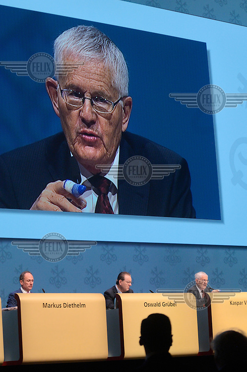 Chairman Kaspar Villiger responds to disgruntled shareholders at the annual general meeting of UBS, Switzerland's largest bank, with the help of a giant video screen. Sat next to him is Oswald Grubel and Markus Diethelm. The Swiss banking industry holds an estimated 4,000 billion Swiss Francs (USD 4,240 billion) in assets, more than half of it foreign, including CHF 880 billion in undeclared European assets alone, benefiting from the country's famous banking secrecy laws.