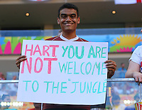 A suporter holds a poster saying 'Hart you are not welcome to the jungle'