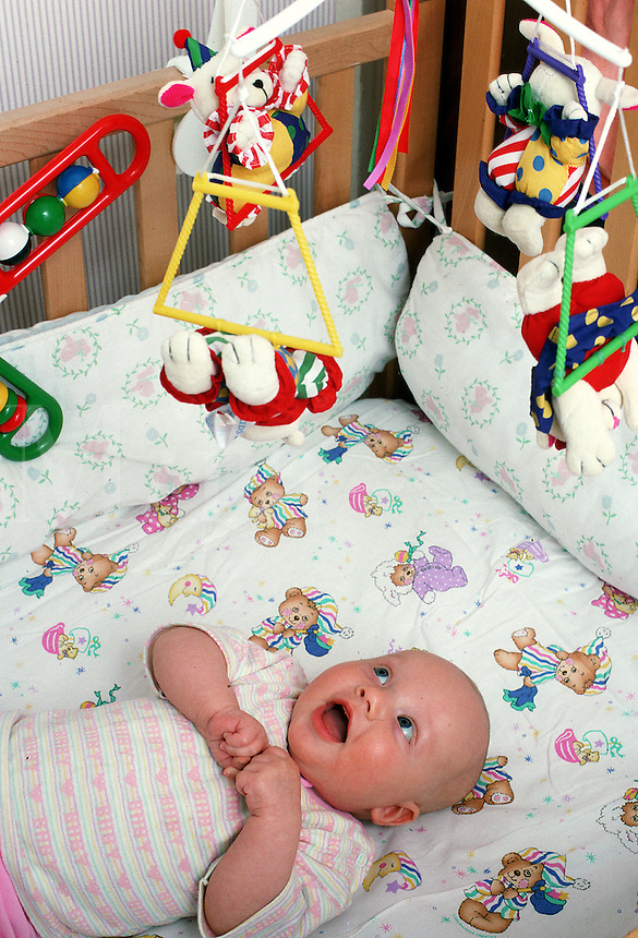 A baby is fascinated by a mobile in its crib.