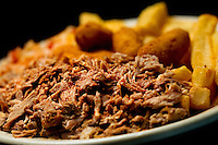 Small business photography of Troutman's Barbecue, a popular BBQ restaurant in downtown Concord, North Carolina. Image shows the BBQ plate served with hush puppies and french fries. Photo is part of a photographic series of images featuring Concord, NC, by photographer Patrick Schneider..