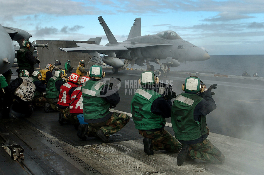 """040601-N-6213R-021 Gulf of Alaska (Jun. 1, 2004) -Flight deck personnel cross their hands, giving the signal for """"Foul Deck"""" to the shooter prior to the launch of an F/A-18C Hornet on the flight deck aboard USS John C. Stennis (CVN 74). With the loud noises from the aircraft on the flight deck, hand signals are essential to proper communications. Stennis and her embarked Carrier Air Wing Fourteen (CVW-14) are currently at sea conducting a scheduled deployment.  Photo by Mark J. Rebilas"""