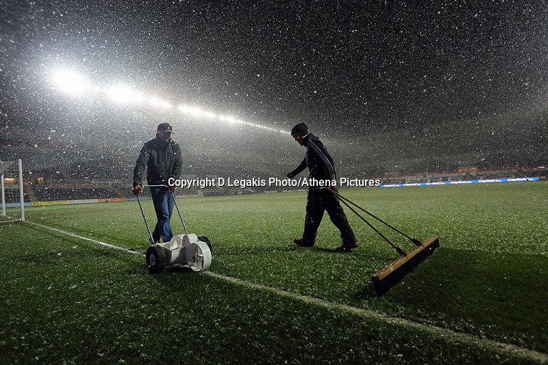 Wednesday 23 January 2013<br /> Pictured: Swansea City FC groundsman Dan Duffy (L) marking fresh lines because of the heavy snow before the long awaited clash tonight, while his colleague is brushing the snow away (R).<br /> Re: Capital One Cup semi-final second leg, Swansea City FC v Chelsea at the Liberty Stadium, south Wales.