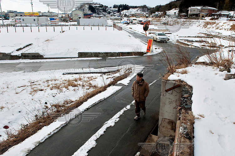 A man walks down a street in what used to be a part of the town of Kesennuma. On 11 March 2011 a magnitude 9 earthquake struck 130 km off the coast of Northern Japan causing a massive Tsunami that swept across the coast of Northern Honshu. The earthquake and tsunami caused extensive damage and loss of life. One year after the earthquake much of the rubble and detritus washed up by the Tsunami has been cleared away but many towns and villages  have not been rebuilt and remain largely deserted. .