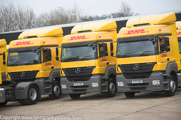 Fleet of yellow DHL heavy goods vehicles parked in the car park of their depot, Martlesham, Ipswich, Suffolk, England