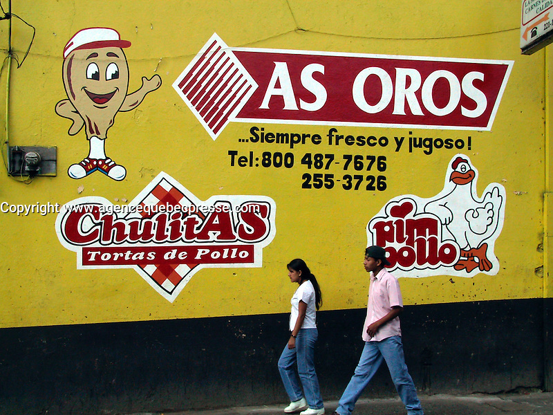 San Jose, COSTA RICA , File Photo -  Jan 23, 2001<br /> Two Costa Ricans pass in front of a wall painted with chicken advertising in downtown San Jose, COSTA RICA on Jan 23rd, 2001