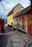 Fine art landscape travel image of old Swedish buildings in Skansen Park, Stockholm, Sweden, with cobble-stone street leading between orange and yellow historic buildings on right and reddish wodden historic structure on left.