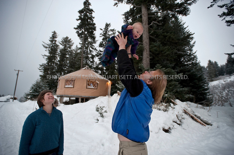 12/11/2009--Seldovia, Alaska, USA..Bretwood Higman (right), Erin McKittrick and their son Katmai, in front of their yurt in Seldovia, Alaska...The yurt is made by Nomad Shelter in Homer, Alaska, and cost about $14,000.  Bretwood Higman ('Hig'), 33 and Erin McKittrick, 30, built it in November, 2008 on land owned by Hig's mother in Seldovia. The yurt is 24' in diameter, the ceiling is over 12' in the middle, 7' around the edge. It has no running water but does have electricity and internet access...McKittrick grew up in Seattle and met Higman, from Seldovia, at Carleton College in 2001.  In June 2007, the couple left Seattle for the Aleutian Islands, traveling 4000 miles solely by human power through some of the most rugged terrain in the world; their adventure has recently been published in a book written by McKittrick with Hig's photographs titled, 'A Long Trek Home: 4,000 Miles by Boot, Raft, and Ski'...Together, the couple also run a small environmental non-profit, Ground Truth Trekking, which uses trekking to explore the complexities of natural resource issues.  The couple lives with their 10 month old son son, Katmai, in Seldovia, Alaska, a 300 person village just off the end of the road system...©2009 Stuart Isett. All rights reserved.
