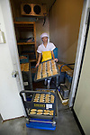 A staffer at Oizen Shoten unloads crates of sasa-kamaboko from a refrigerator at the company's factory in Tome City, Miyagi Prefecture, Japan on 11 Sept. 2012.  Photographer: Robert Gilhooly