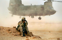 Sheilding herself from the wash of sand and dust US Army Captain Twila Peterson sits on a dirt mound as the CH-47 Chinook takes off. The Chinooks are used to shuttle personnel and equipment from Camp Doha and Camp Udairi  in a run referred to as the log(logistics run) run. The Chinook is knicknamed Big windy for the amount of wind it produces with two large three rotor blades.