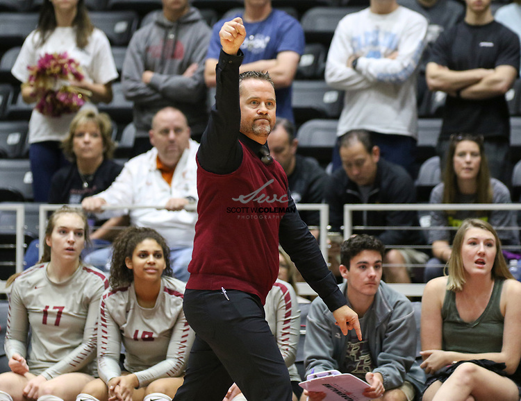 Rouse Raiders head coach Jacob Thompson raises a fist as his team scores a point during a Class 5A girls high school semifinal volleyball game between Rouse High School and Aledo High School at Curtis Culwell Center in Garland, Texas, on November 17, 2017. Rouse swept Aledo (25-17, 27-25, 25-18) to advance to the finals.