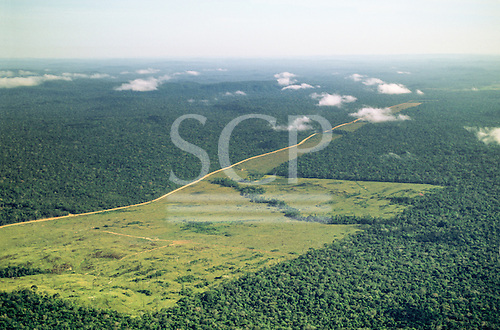 Amazon, Brazil. Aerial view of Rainforest with large areas cleared for farming and cattle ranching; dirt road along an indian reserve.