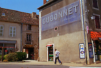 A village in Cote Chalonnaise (Bourgogne) with a man walking under an old faded advertisement for Dubonnet