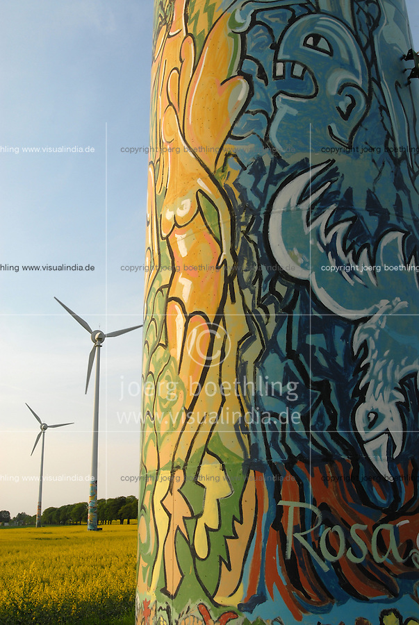 GERMANY, Wismar, village Luebow, yellow rape seed plant and Enercon windturbine with art painting / DEUTSCHLAND, Wismar, Rapsbluete und Windpark mit von Kuenstlern bemalten Enercon E-66 Windraedern in Lübow