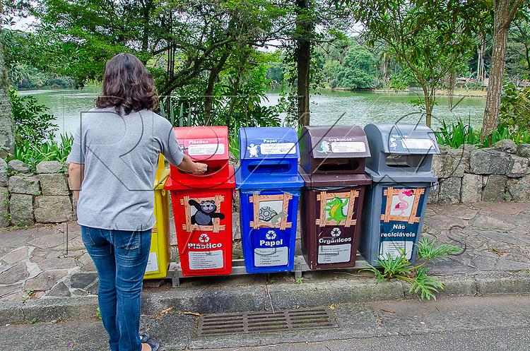Mulher jogando lixo em lixeira para coleta seletiva na Fundação Parque Zoológico de São Paulo, São Paulo - SP, 02/2016. Uso de imagem autorizado.