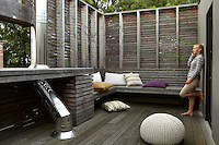 An enclosed decked terrace opens out from one of the bedrooms, an integrated bench strewn with cushions