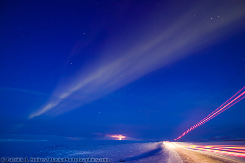 Aurora borealis streaks the sky over the Arctic coastal plains at dusk, exhaust from pump station three of the Trans Alaska Oil pipeline is illuminated by the station lights. Lights from a passing truck light the James Dalton Highway. Arctic Alaska.