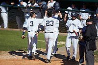 Zach Almond (23) of the Catawba Indians is greeted by teammates after his second home run of the game against the Wingate Bulldogs at Newman Park on March 19, 2017 in Salisbury, North Carolina. The Indians defeated the Bulldogs 12-6. (Brian Westerholt/Four Seam Images)