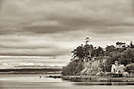 A large house sits along the shore of Whidbey Island with a private dock on a cloudy day.