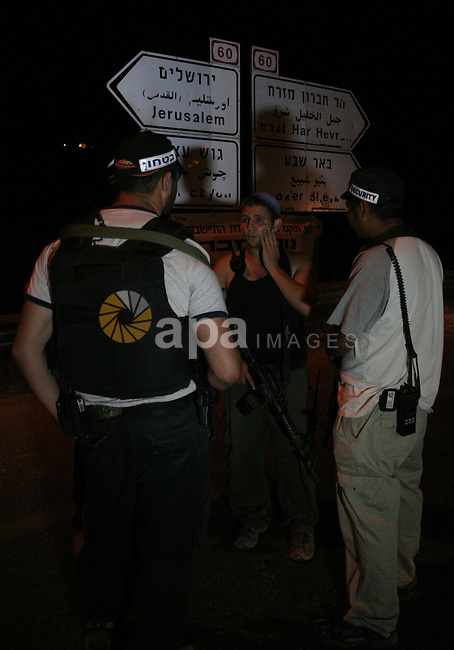 Israeli border policemen block the road after a settlers' car was ambushed by Palestinian gunmen killing two woman and two men next to Kiryat Arba settlement in the southern West Bank August 31, 2010. The military wing of the Islamist Hamas said it was behind the killing of four Israelis in an attack near the West Bank settlement of Kiryat Arba today. Photo by Mamoun Wazwaz
