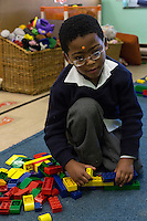South Africa, Cape Town.  A Visually-impaired Young Boy Assembles Lego Pieces by Touch.   Athlone School for the Blind.