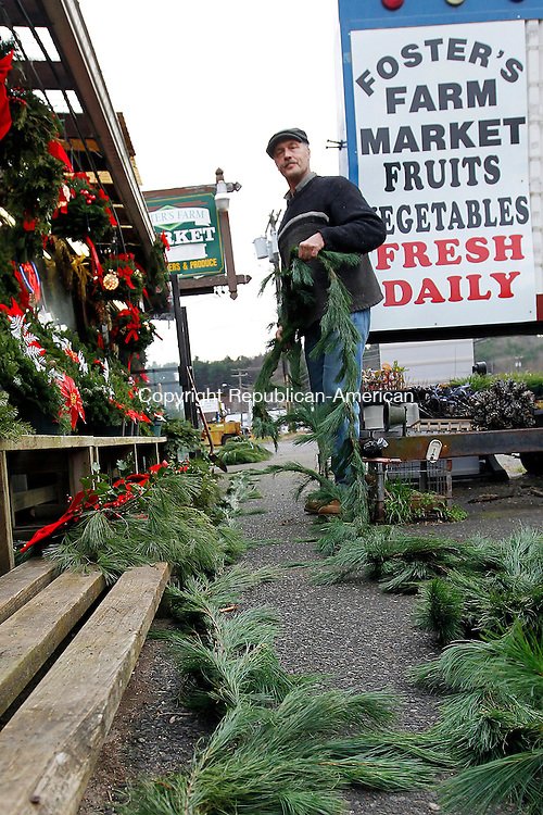 Thomaston, CT-30 November 2011-112911CM02-  Mark Foster of Foster's Farm Market puts together pine roping outside his store in Thomaston Tuesday afternoon.  The roping, which is used for holiday decoration is one of the many items Foster was getting ready for the season.  Also on display were wreaths, kissing balls and cemetery boxes.  Christopher Massa Republican-American