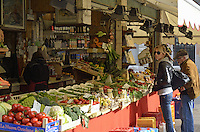 Woman and mature man buying vegetables at Rialto Market, Venice, Italy