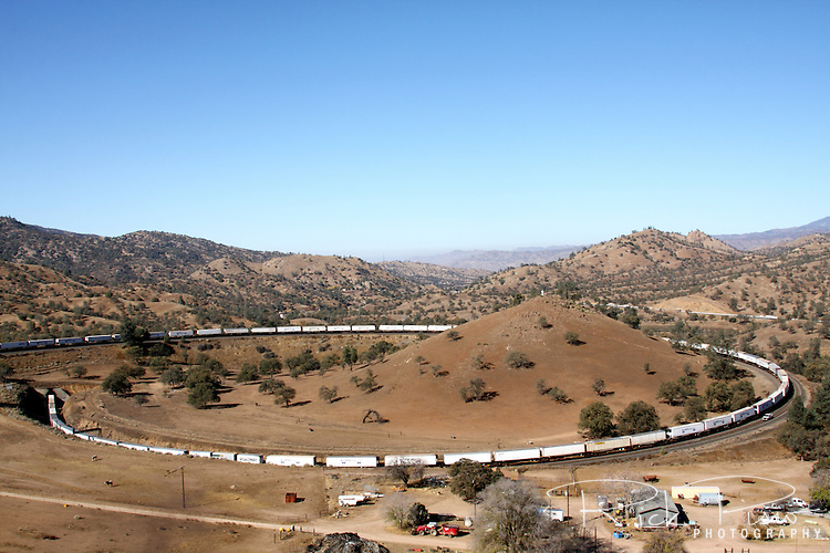 An eastbound BNSF freight train passes over itself at the Tehachapi Loop between Bakersfield and Mojave, California. The Tehachapi Loop is a .73 miles (1.17 km) long 'spiral', or helix, on the railroad main line. A train more than 4,000 feet (1.2 km) long (about 85 boxcars) will pass over itself going around the loop. In 1998 it was named a National Historic Civil Engineering Landmark.