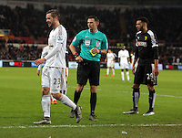 Match referee Michael Oliver (C) having just shown a yellow card to Gylfi Sigurdsson of Swansea (L) for protesting about the position of Etienne Capoue of Watford (R) during the Barclays Premier League match between Swansea City and Watford at the Liberty Stadium, Swansea on January 18 2016