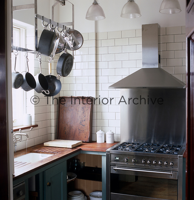The industrial-style kitchen is well equipped with a stainless steel range cooker and a large collection of saucepans