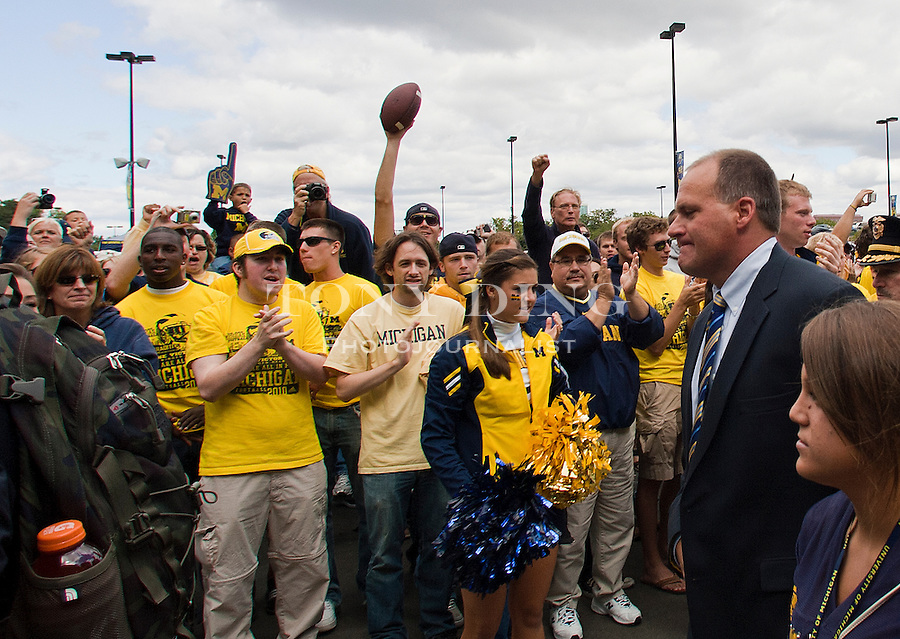 Michigan head coach Rich Rodriguez, right, walk with his team and cheering fans to Michigan Stadium before an NCAA college football game with Connecticut, Saturday, Sept. 4, 2010, in Ann Arbor, Mich. (AP Photo/Tony Ding)