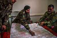 DASH-E TOWP, WARDAK PROVINCE, AFGHANISTAN - NOVEMBER 5, 2013: (C) Lt. Col. Mohammad Daowood points to positions on a map of the Chak valley planning for a re-supply mission with General Razaq on November 5, 2013 at the Dash-e Towp base, Afghanistan.