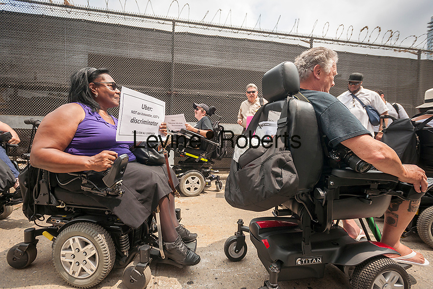 """Members of the Taxis For All Campaign and their supporters protest in front of Uber headquarters in West Chelsea in New York on Thursday, July 30, 2015. The protesters had a """"roll-in"""" calling on the company to stop discriminating against the disabled by requiring handicapped accessible vehicles. Out of 20,777 Uber cars on the road not one of them is wheelchair accessible. (© Richard B. Levine)"""