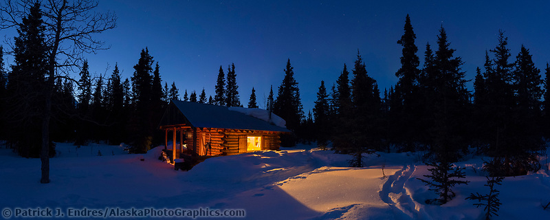Rustic log cabin at dusk in the Alaska Range mountains, Interior, Alaska.