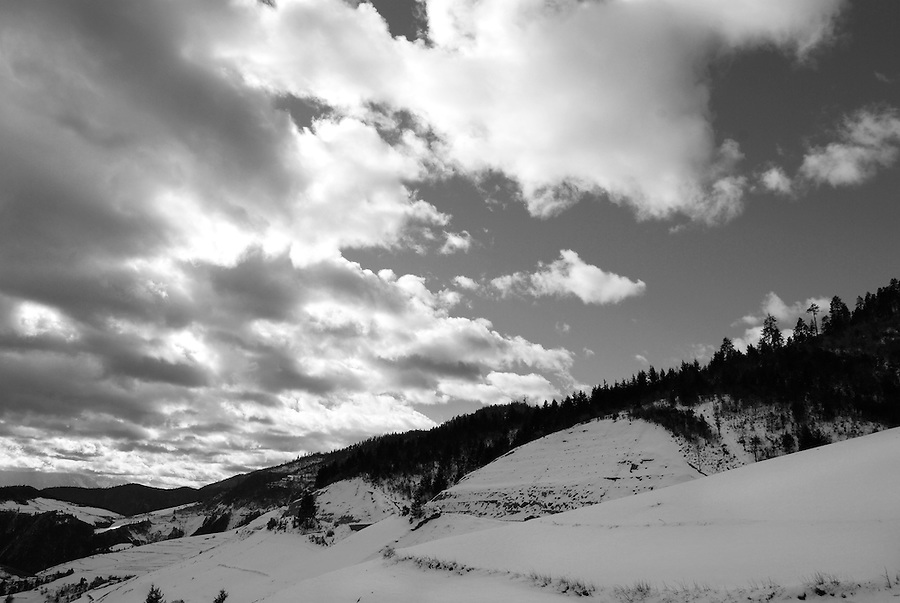 A scenic and spectacular view of outdoor high mountains covered in thick snow. Black and white nature fine art photography by Paul Chong.