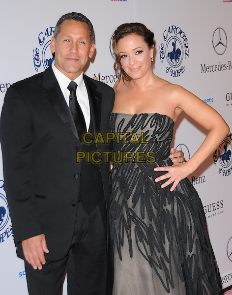 ANGELO PAGAN & LEAH REMINI .at The 32nd Annual Carousel of Hope Ball held at The Beverly Hilton hotel in Beverly Hills, California, USA, .October 23rd 2010..half length strapless black grey gray dress hand on hip tulle gown  suit tie married husband wife couple                                                                         .CAP/RKE/DVS.©DVS/RockinExposures/Capital Pictures.