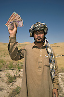 A man holds up a handful of Afghani notes. He received the money for a cash-for-work scheme. This is a short-term intervention used by some humanitarian assistance organisations to provide temporary employment in public projects, such as repairing roads, clearing debris or rebuilding infrastructure.