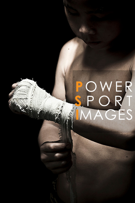 """10 years old Muay Thai Kickboxing figther poses at Sangmorakot gymnasium in Bangkok, Thailand. Muay Thai, also know as """"Art of Eight Limbs"""", is a hard martial art and Thailand's national sport. Photo by Victor Fraile --- Image by © Victor Fraile"""
